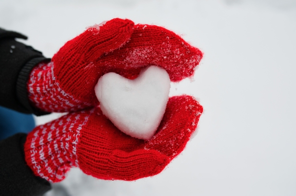 Snowball shaped in a heart being held by red mittens