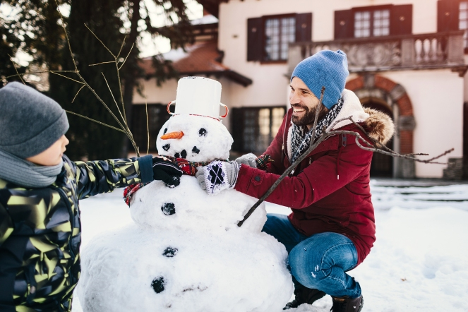 Family Having Fun Outdoors At Winter Time. Father and son making snowman and enjoying the winter day.