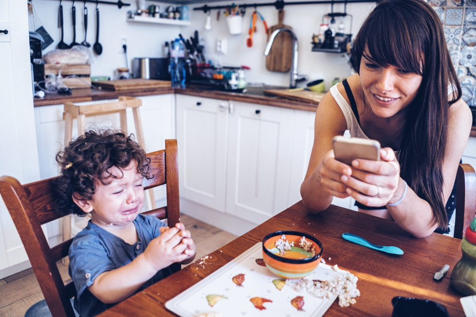 Toddler crying after making mess with his food while parent uses smart phone