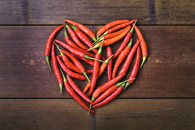 Chili heart on bamboo background