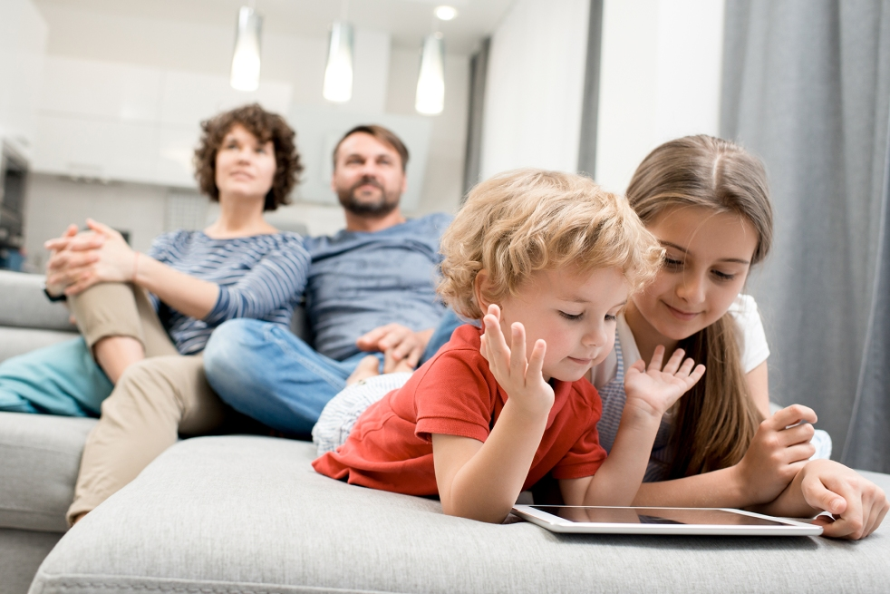 siblings lying on cozy couch and playing game on digital tablet while their parents wrapped up in watching TV, interior of studio apartment on background