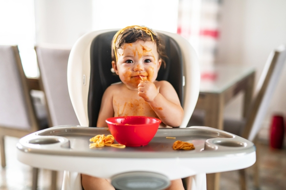 Child sitting in highchair eating spaghetti that has gotten all over their head, face, hands