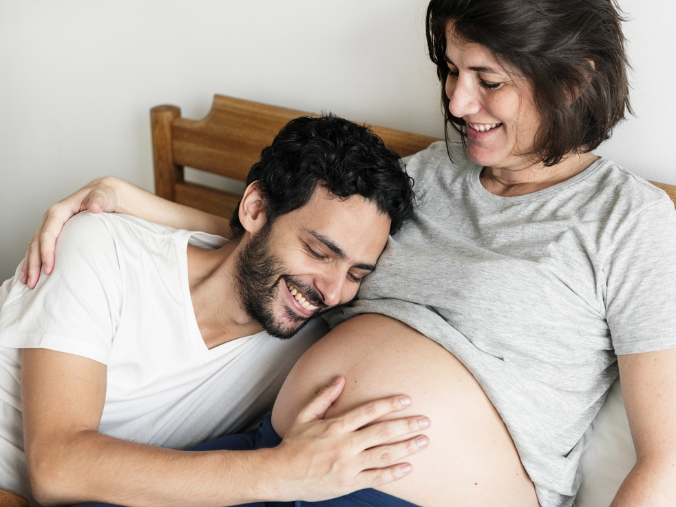 Couple lying in bed together holding and looking at pregnant tummy