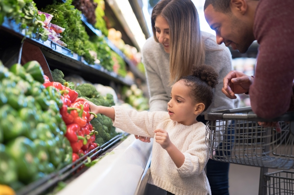 A pre-school age child helps parents pick out veggies in the produce section at the grocery store.