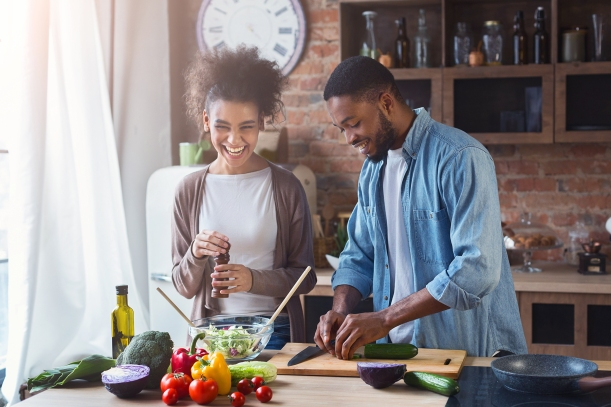 young couple laughing and preparing salad in kitchen