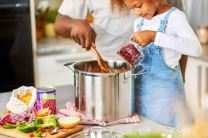 Parent and child cooking in kitchen. Child pouring red beans from measuring cup into large stainless steel pot while parent holds wooden spoon in pot