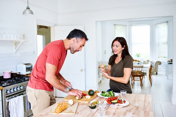 Pregnant individual and partner preparing a healthy meal together in the kitchen