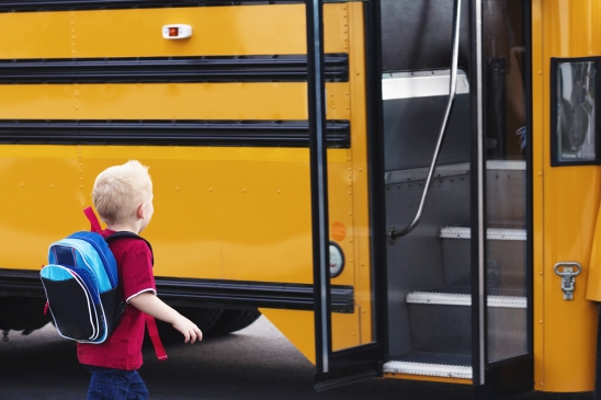 A young child is ready to board a school bus and go to elementary school
