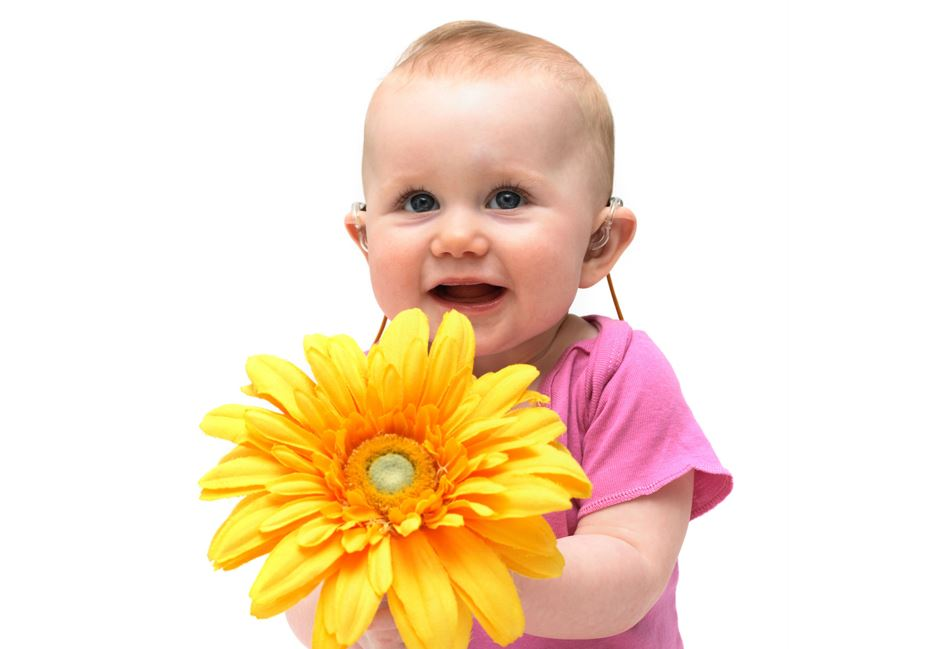 Baby wearing a pink shirt, holding a large yellow flower.