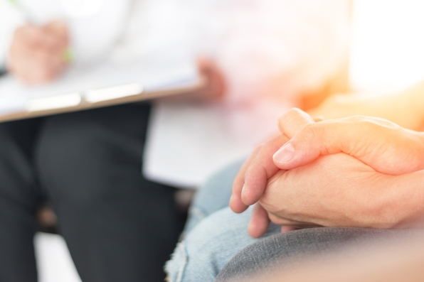 Close up of couple holding hands with person taking notes on clipboard in background