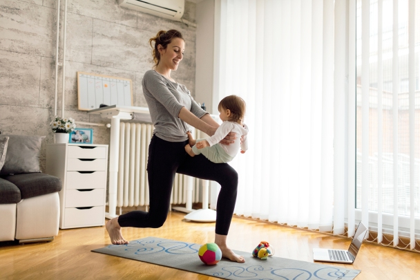 Parent at home holding baby on knee while doing lunges to exercise