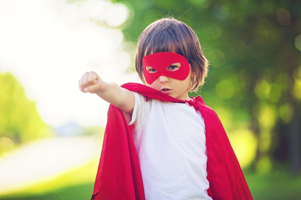 Preschool child wearing a red eye mask and red cape. Playing superhero in the park