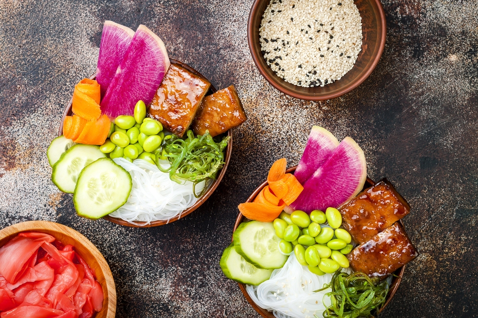 Vegan tofu poke bowls with seaweed, watermelon radish, cucumber, edamame beans and rice noodles.