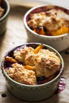 Fruit cobbler with biscuit topping in individual ramekins, just out of the oven.
