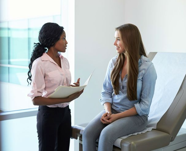 young adult talking to health care professional in an exam room