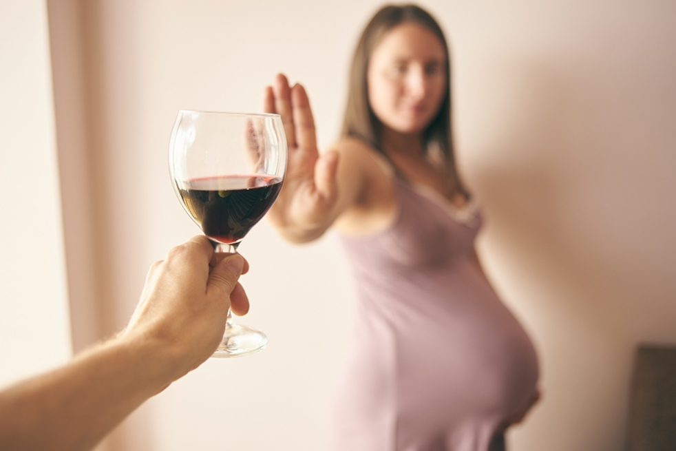 Pregnant individual with hand up refusing glass of red wine