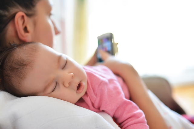 Parent sitting in bed holding sleeping baby while checking mobile phone