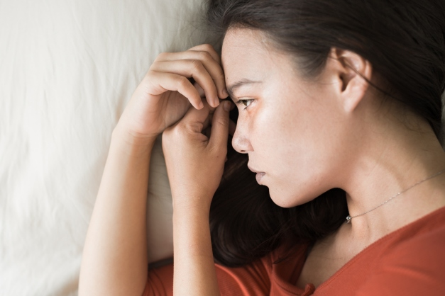 Woman lying on her side in bed looking sad and depressed
