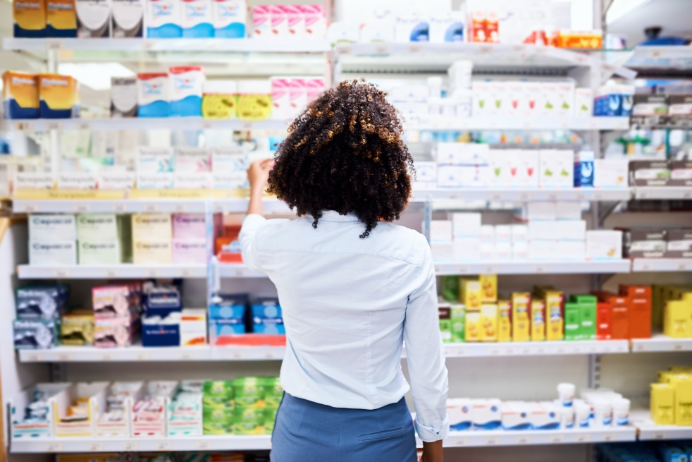 Rearview shot of a young woman looking at products in a pharmacy