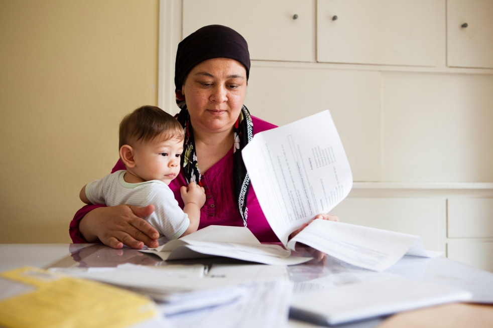 Individual with scarf sits with baby in lap at table full of paperwork.