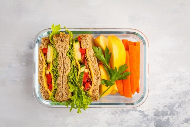 sandwich and veggies in a glass container