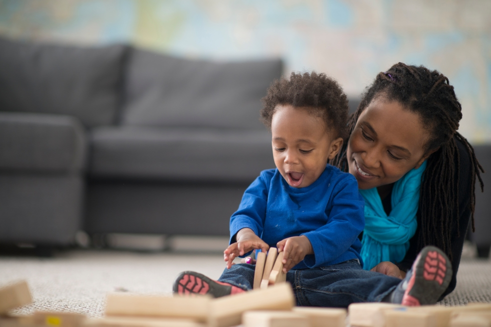 Parent and toddler playing with wooden blocks together on the floor