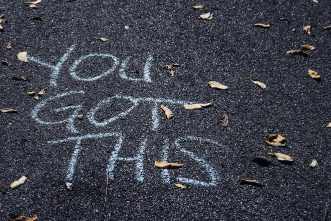 The words YOU GOT THIS written with white sidewalk chalk on a black gravel