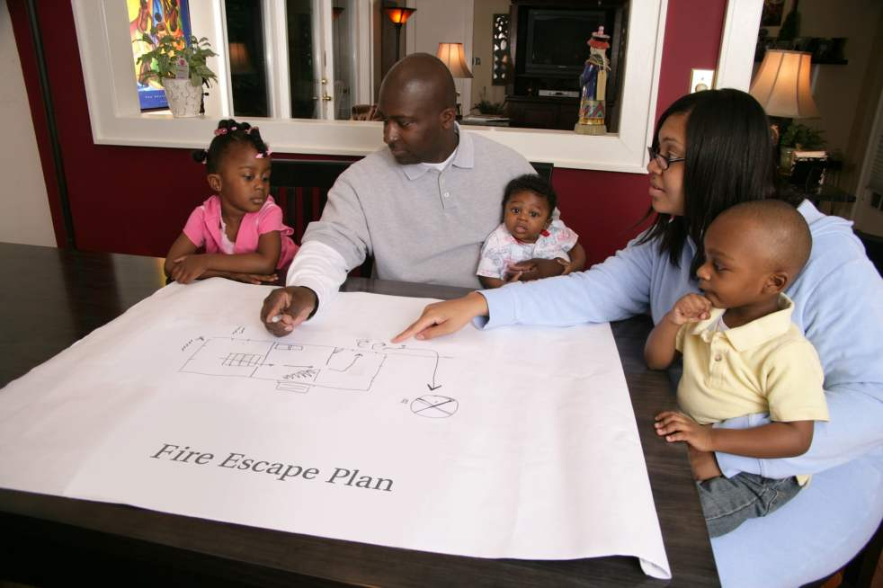Family sitting at table planning their Fire Escape Plan