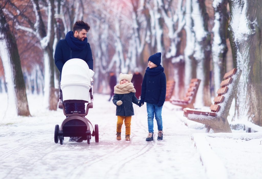Parent taking a walk outdoors in the winter pushing a stroller with toddler and older child holding hands walking beside the stroller
