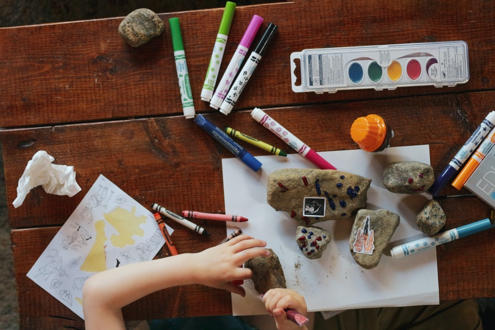 Child doing crafts at wooden table with markers, rocks and paper.
