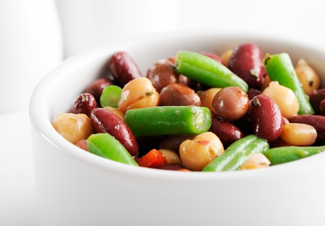 Colorful mixed beans salad in a white bowl, on a white background